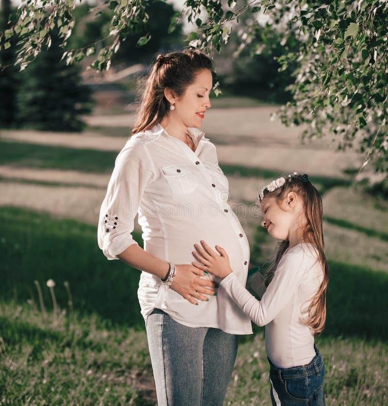 Ma?a dziewczynka i jej szcz??liwa ci??arna mama na spacerze w lato parku zdjęcia stock
