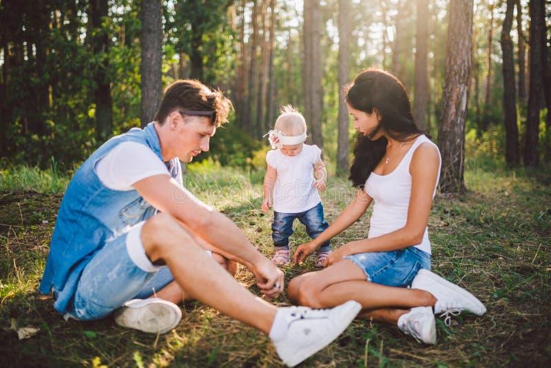 Ma?a dziewczynka jeden rok na tle k?ama na trawa uczenie chodzi? na naturze w parku rodzice odpoczywa pierwsze kroki obraz stock