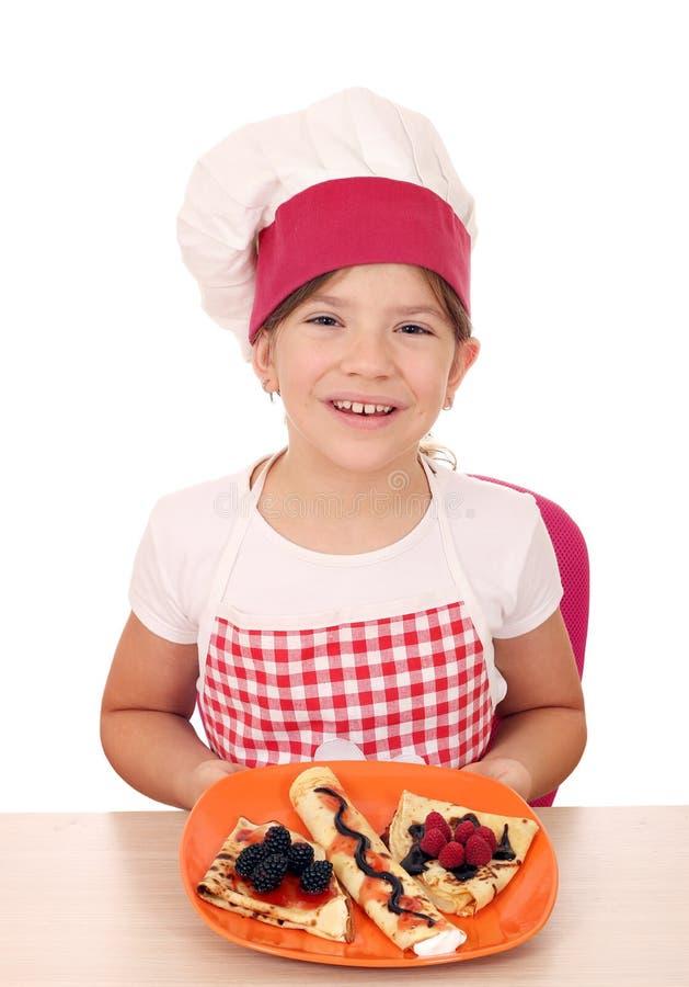 Ma?a dziewczynka kucharz z s?odkimi krepami na talerzu zdjęcia royalty free