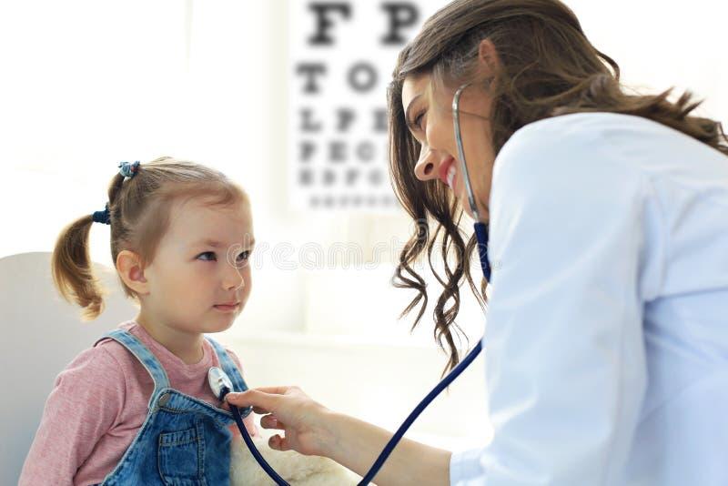 Ma?a dziewczynka przy lekark? dla checkup Doktorska kobieta auscultate bicie serca dziecko obrazy stock