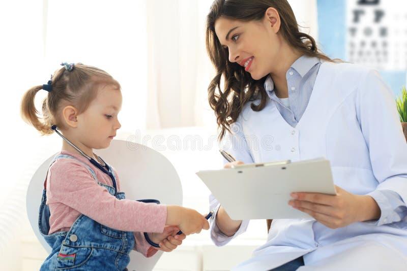 Ma?a dziewczynka przy lekark? dla checkup Dziecko auscultate bicie serca lekarka zdjęcia royalty free