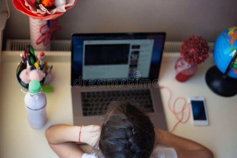 Ma?a dziewczynka robi jej pracie domowej na laptopie zdjęcie royalty free
