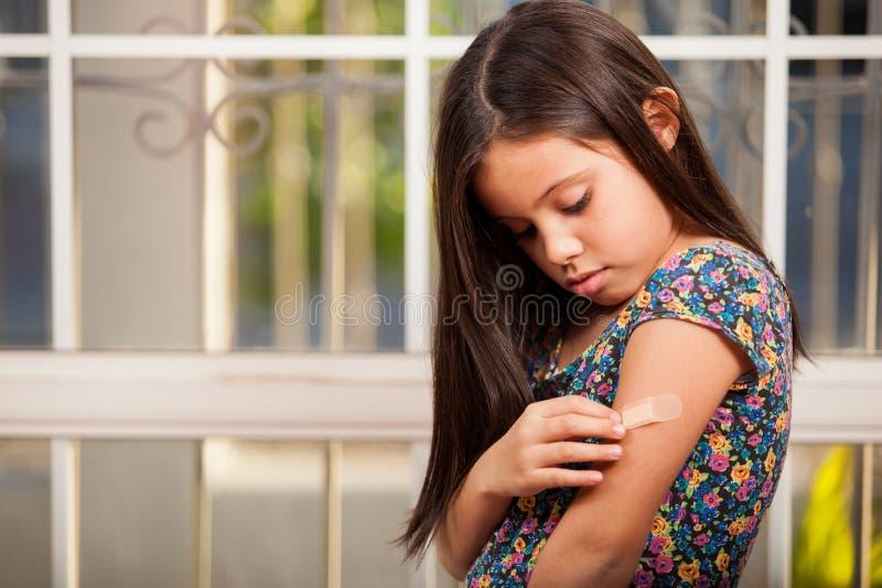 Mała Dziewczynka Stawia Pomoc Dalej Zdjęcie Stock