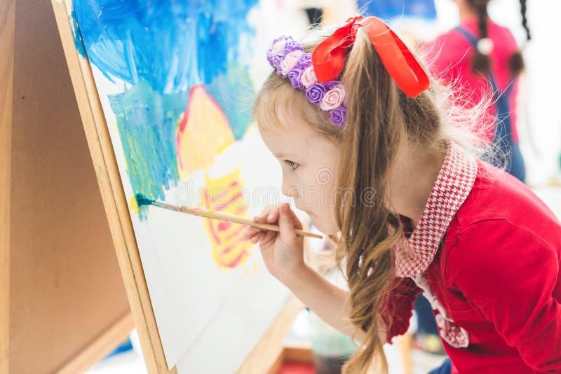 Ma?a dziewczynka z nauczycielem w grupie preschool ucze? siedzia? rysunek obrazek Maluj?cy na maelbert, paleta i obraz royalty free