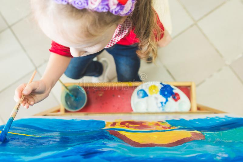 Ma?a dziewczynka z nauczycielem w grupie preschool ucze? siedzia? rysunek obrazek Maluj?cy na maelbert, paleta i zdjęcie royalty free
