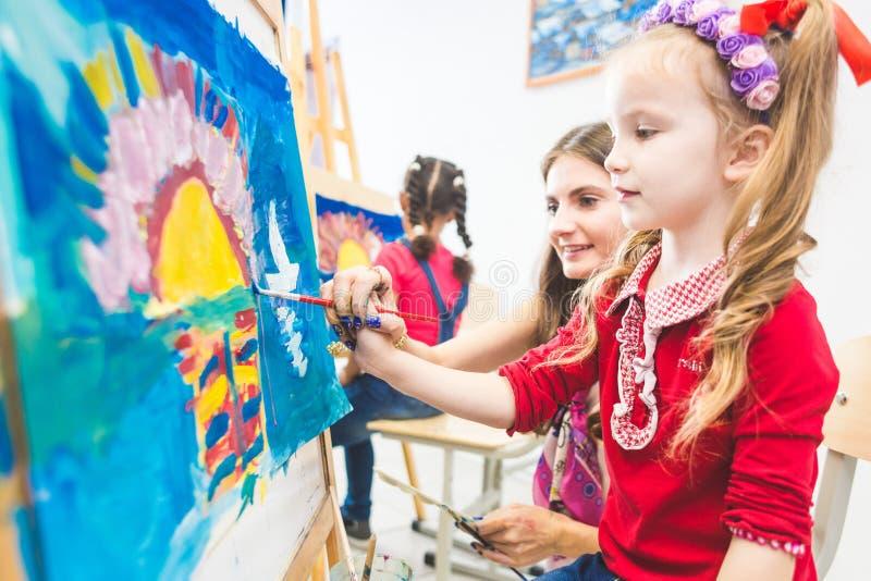 Ma?a dziewczynka z nauczycielem w grupie preschool ucze? siedzia? rysunek obrazek Maluj?cy na maelbert, paleta i fotografia royalty free
