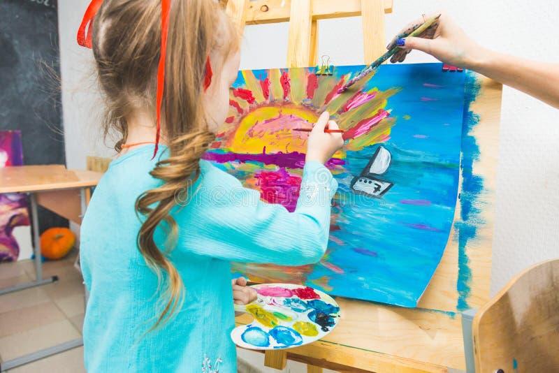 Ma?a dziewczynka z nauczycielem w grupie preschool ucze? siedzia? rysunek obrazek Maluj?cy na maelbert, paleta i obraz stock