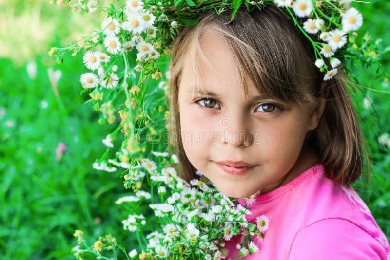 Ma?a dziewczynka z wiankiem kwiaty na ona kierownicza fotografia stock