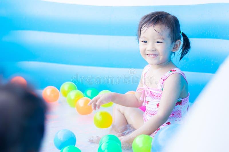 ma?e dziecko cieszy si? zabaw? bawi? si? wod? i w nadmuchiwanym basenie z kolorowym ma?e pi?ki zdjęcie stock