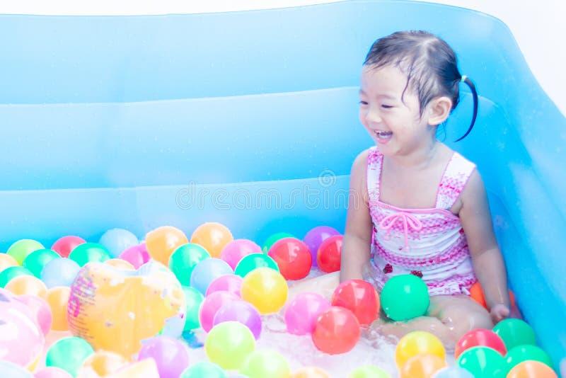 ma?e dziecko cieszy si? zabaw? bawi? si? wod? i w nadmuchiwanym basenie z kolorowym ma?e pi?ki obrazy stock