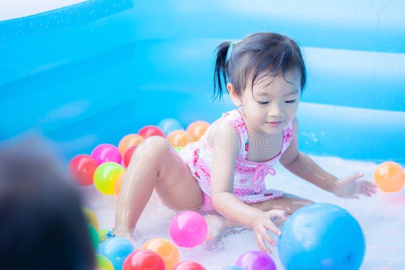 ma?e dziecko cieszy si? zabaw? bawi? si? wod? i w nadmuchiwanym basenie z kolorowym ma?e pi?ki zdjęcie royalty free