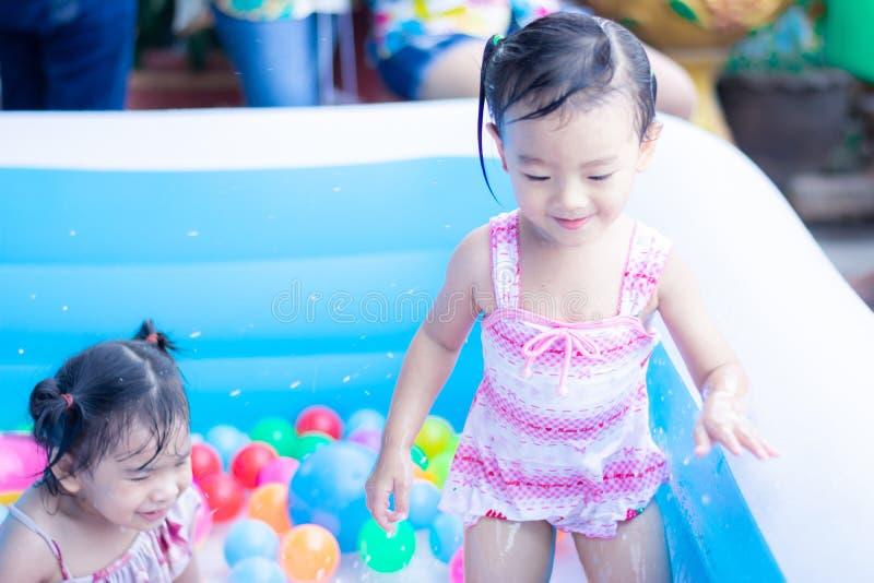ma?e dziecko cieszy si? zabaw? bawi? si? wod? i w nadmuchiwanym basenie z kolorowym ma?e pi?ki fotografia royalty free