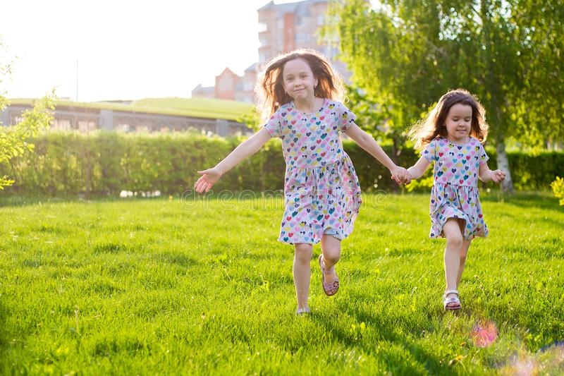 Ma?e szcz??liwe dziewczyny na spacerze na lato wiecz?r przy zmierzchem w parku siostry fotografia royalty free