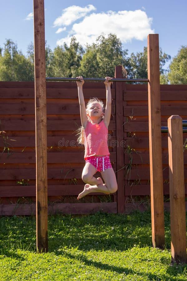 Ma?ej dziewczynki obwieszenie na horyzontalnym barze fotografia royalty free
