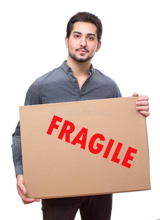 MA joven que sostiene el envío frágil de la cartulina imagenes de archivo