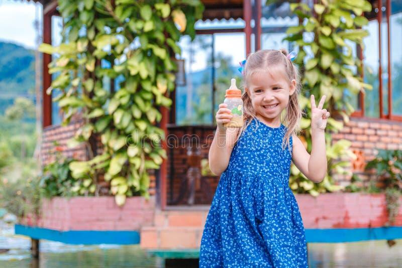 Ma?a pi?kna dziewczyny pozycja z butelk? rybi jedzenie w r?ce Yang zatoka Wietnam zdjęcie stock