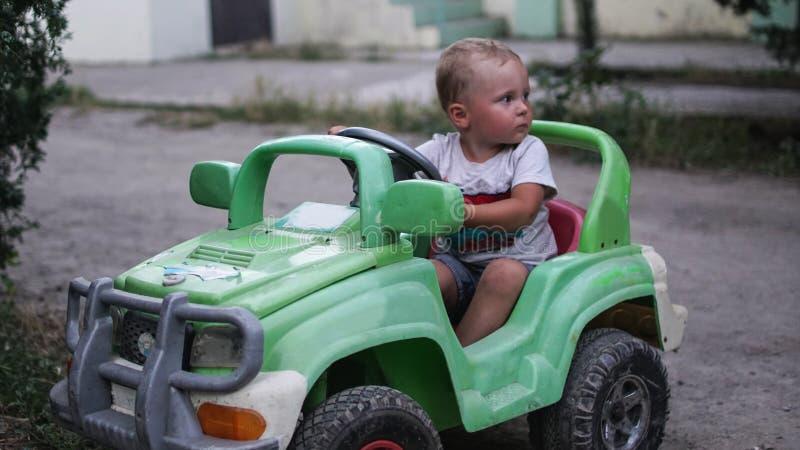 Ma?a preschool ch?opiec jedzie du?ego zabawkarskiego samoch?d i ma zabaw?, outdoors fotografia stock