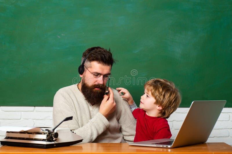 Ma?tre d'?cole et ?tudiant ?l?mentaires dans la salle de classe Professeur et ?colier ? l'aide de l'ordinateur portable dans la c photo libre de droits