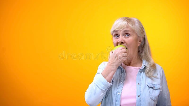 Ma?? verde fresca cortante da senhora idosa otimista, dentes saud?veis, stomatology imagem de stock