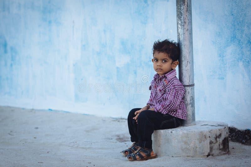MAAFUSHI MALDIVES, STYCZEŃ, - 5, 2013: Mała Maldivian chłopiec z głębokimi poważnymi oczami pozuje blisko błękitnej ściany obrazy royalty free