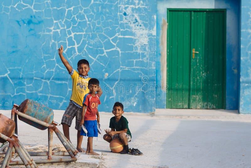 MAAFUSHI MALDIVES, STYCZEŃ, - 5, 2013: Trzy bosonogiego Maldivian dzieciaka w kolorowych koszulkach przyciągają fotograf uwagę obrazy stock