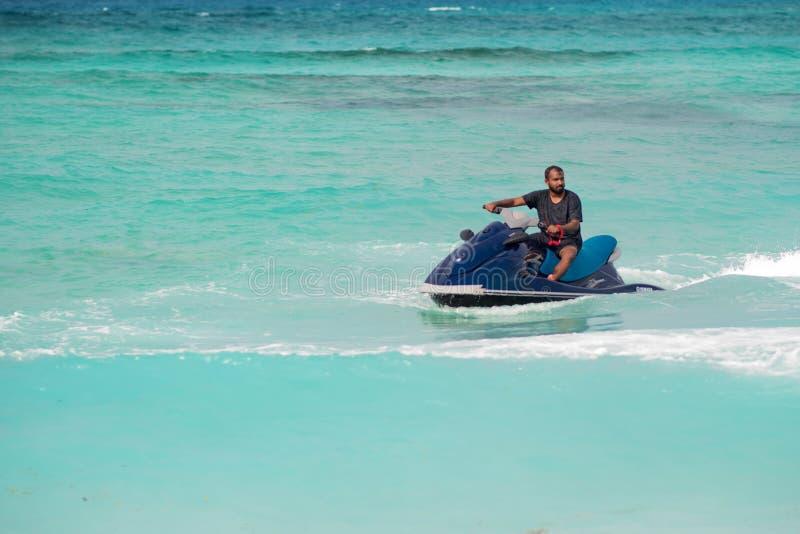 MAAFUSHI, MALEDIVEN - 9. DEZEMBER 2018: Bewohner der Malediven auf einem jetski Mann auf einem Wasserfahrzeug macht eine Wendung lizenzfreie stockbilder