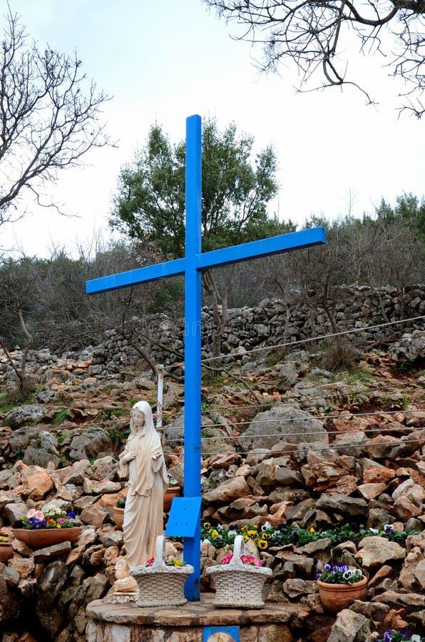 Maagdelijke Mary en het kruis bij Katholieke bedevaartplaats Medjugorje Bosnië - Herzegovina stock foto's