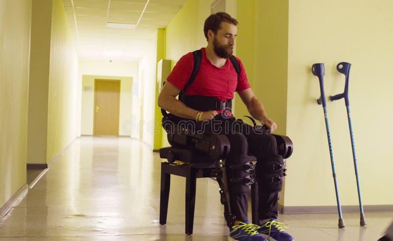 Maak de mens in de robotachtige exoskeleton zitting op de bank onbruikbaar stock afbeeldingen
