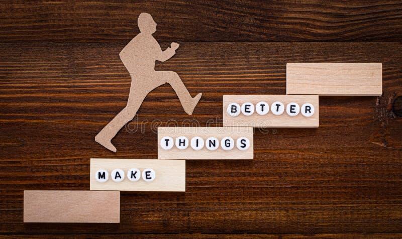 Maak dingen beter - het Concept van de Verbetering Papieren man beklimt de stappen naar succes in een conceptueel beeld boven een stock foto