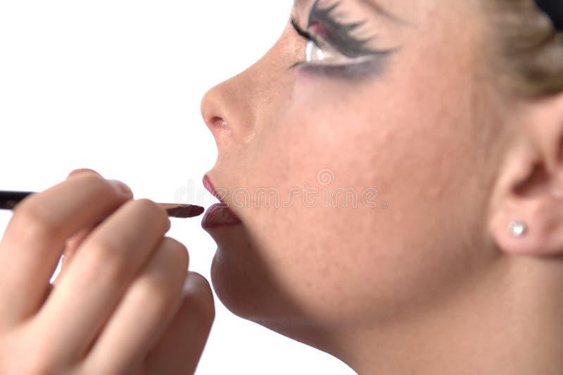 Maak omhoog kunstenaar die lippenstift toepast stock afbeeldingen