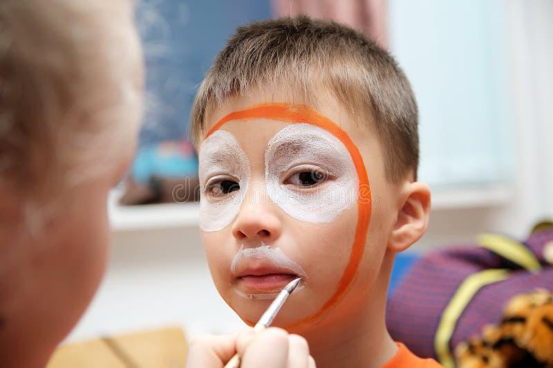 Maak omhoog kunstenaar die tijgermasker voor kind maken De kinderen zien het schilderen onder ogen De jongen schilderde als tijge stock afbeeldingen