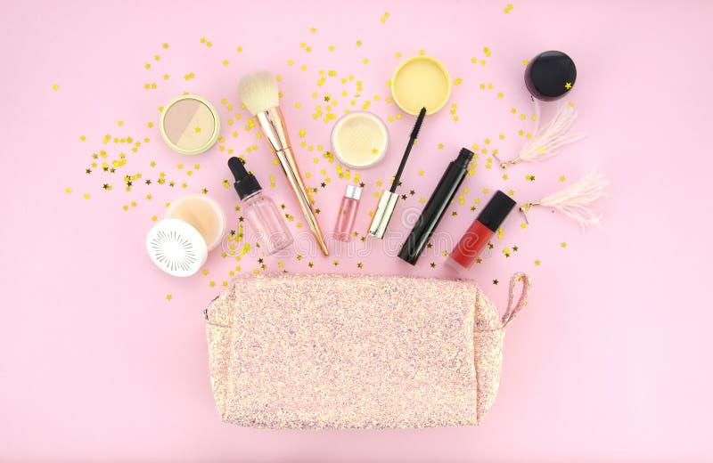 Maak omhoog zak en reeks van professionele decoratieve schoonheidsmiddelen, make-uphulpmiddelen en toebehoren op roze achtergrond stock afbeeldingen