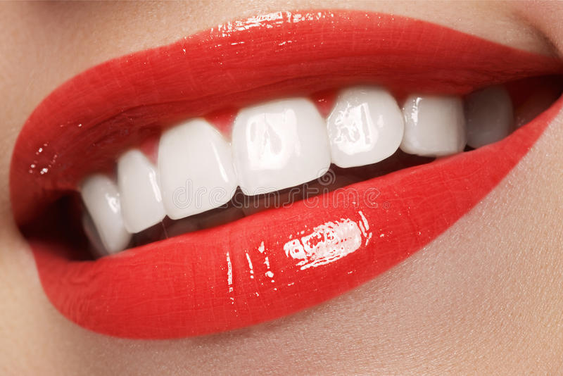 Maakt de close-up gelukkige vrouwelijke glimlach met gezonde witte tanden, heldere rode lippen op De kosmetiek, tandheelkunde en  stock afbeeldingen