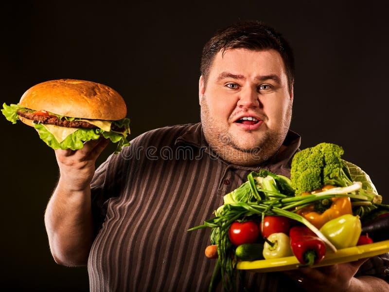 Maakt de dieet vette mens keus tussen gezond en ongezond voedsel stock afbeelding