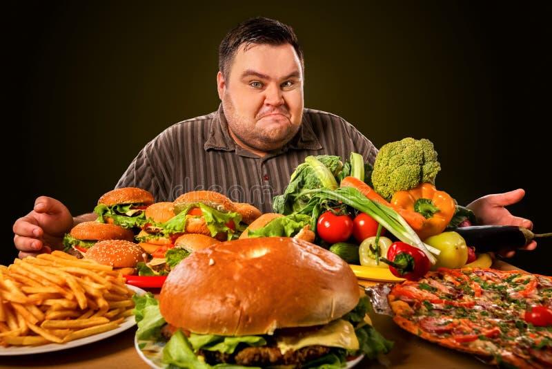 Maakt de dieet vette mens keus tussen gezond en ongezond voedsel stock foto's