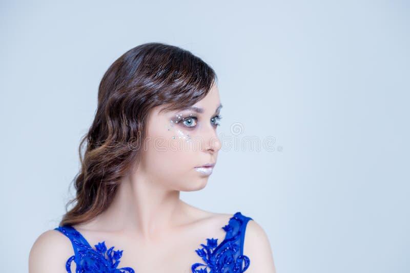 Maakt de schoonheids modelvrouw met mooi omhooggaande en krullende haarstijl over witte achtergrond, magische gloed De viering va stock afbeeldingen