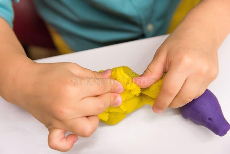 Maakt de vier éénjarigen Kaukasische jongen met handen dierlijke cijfers van modellerings gele klei op wit tafelblad De kleutersc stock foto's