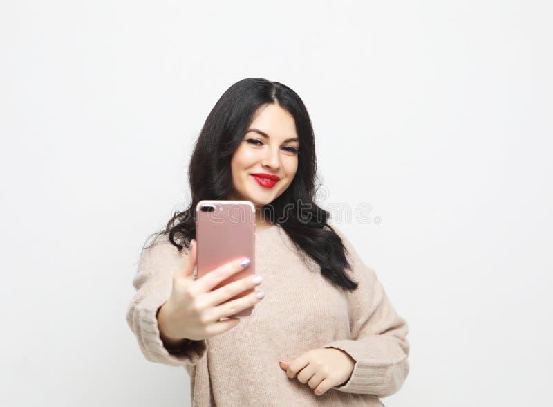 Maakt het manier curvy donkerbruine meisje die foto nemen zelfportret op smartphone royalty-vrije stock afbeeldingen