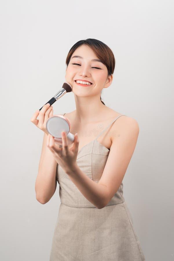 Maakt het schoonheids donkerbruine meisje die pret hebben en gekscheren met omhoog en gezichtspoeder stock foto's