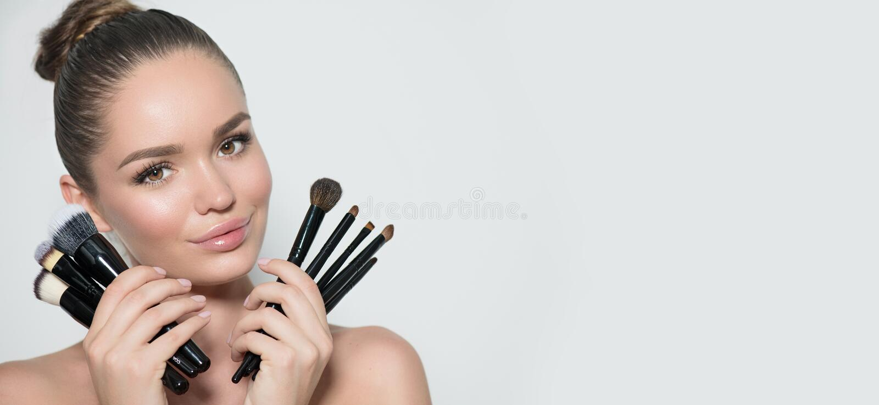 Maakt het schoonheids modelmeisje, de holdingsreeks van de make-upkunstenaar van omhoog borstels en het glimlachen Mooie donkerbr stock afbeeldingen