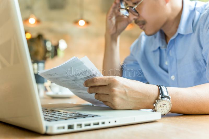 Maakt zich zakenmanhanden op zijn hoofd ongerust bekijkend document met laptop op lijst stock foto