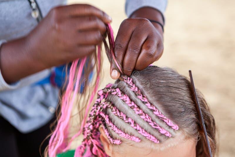 Maakte de Afro Amerikaanse kapper vlechten in Afrikaanse stijl voor jong Kaukasisch meisje, close-up stock afbeeldingen