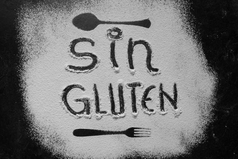 Maakte de gluten vrije bloem met tekstgluten vrij in Spaanse taal met lepel en vorksilhouet met bloem op donkere textuur stock foto