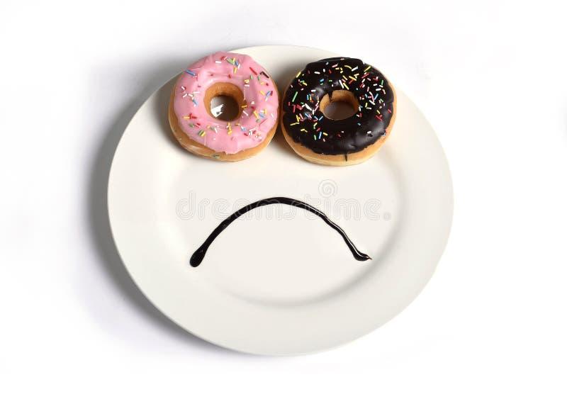Maakte het Smiley droevige gezicht op schotel met donuts als ogen en de mond van de chocoladestroop in dieet en voeding van de su stock afbeeldingen