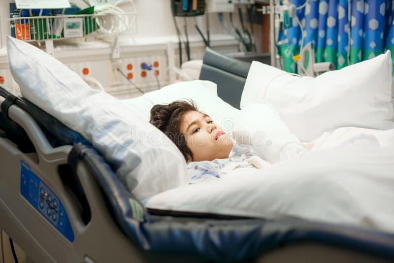 Maakte weinig jongen onbruikbaar liggend ziek in het ziekenhuisbed stock afbeelding