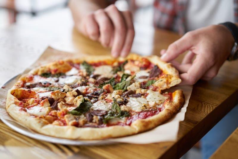 Maaltijdtijd bij pizzeria, mens die een plak van de pizza neemt stock afbeeldingen