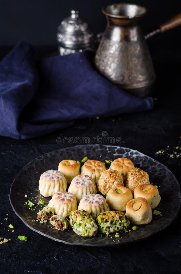 Maamoul ou mamoul - les biscuits arabes ont bourré des dates ou le phistachio avec le glaçage cugar sur le fond foncé Foyer sélec photos libres de droits