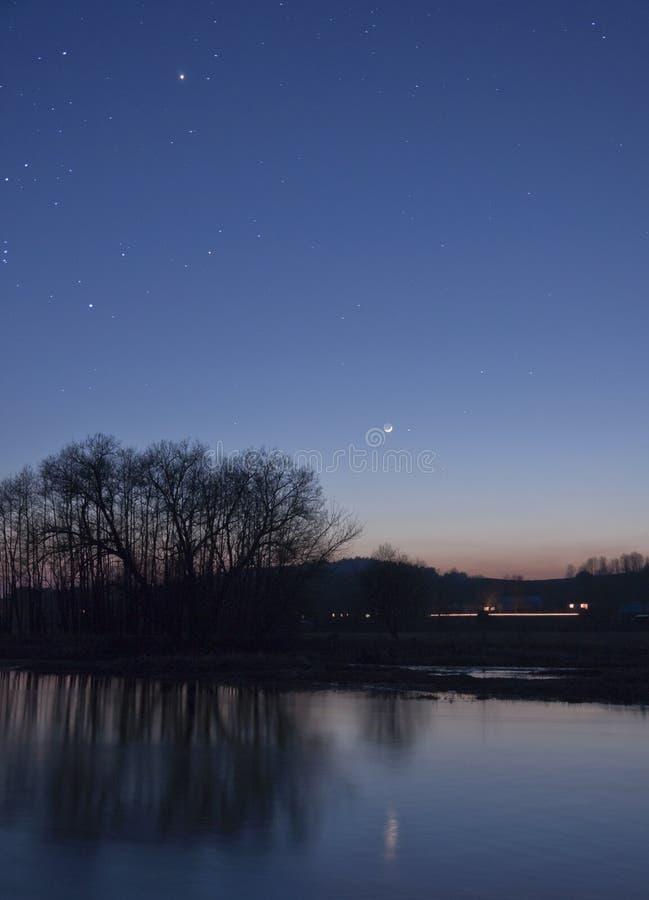 Maan en sterren over rivier stock fotografie