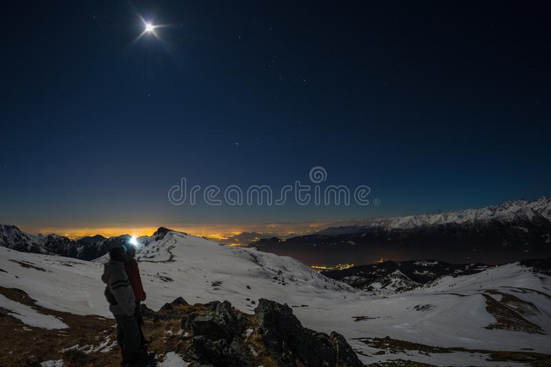 Maan en sterrige hemel, sneeuw op de Alpen, fisheye lens Orion Constellation, Betelgeuse en Sirio De lange blootstelling vertroeb stock foto's