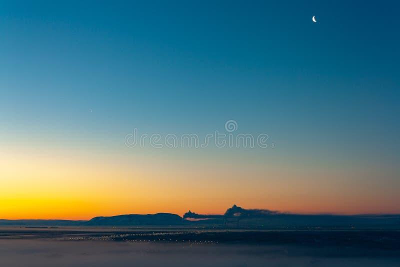 Maan en Venus over industriële stad, Norilsk stock foto
